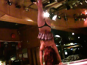 Sexy brunette pole dancer takes off her clothes on the stage