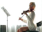 Libidinous babe playing violin and masturbating her pussy