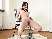 Tied up pallid brunette sits on the chair and pisses in the jar in empty room