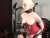 Juggy blonde wearing red corset and having pierced nipples gets her pussy punished