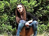 Slim dark haired chick in sunglasses pisses in woods