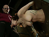 Locked into the pillory short haired brunette gets nipples pinned with toys