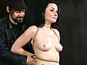 Tattooed nude brunette is tied up and punished in the torture room