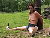 Topless red haired chick is sitting on the ground and waiting for master