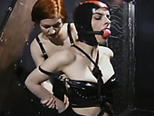 Dirty-minded chubby redhead makes submissive brunette wear latex stuff