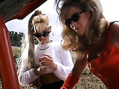 Two light haired classy babes in red gloves pet pussies with toy in car