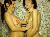 Slim redhead helps to wash ugly curly brunette oldie and tickles her cunt