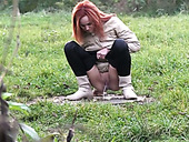 Kinky shameless redhead squats down to piss outdoors on the grass