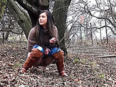 Kinky long haired brunette gal pulls down jeans and pisses outdoors