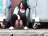 A bit plump amateur brunette gal squats down and pisses between refuse bins