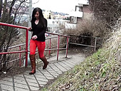 Dark haired nympho pulls down her bright red pants to pee on public path