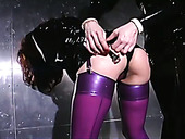 Dirty-minded latex domme slaps submissive chick's booty with lash