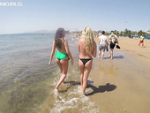 Two topless girlfriends are walking along the beach