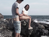 Young couple is making love on the rocky shore